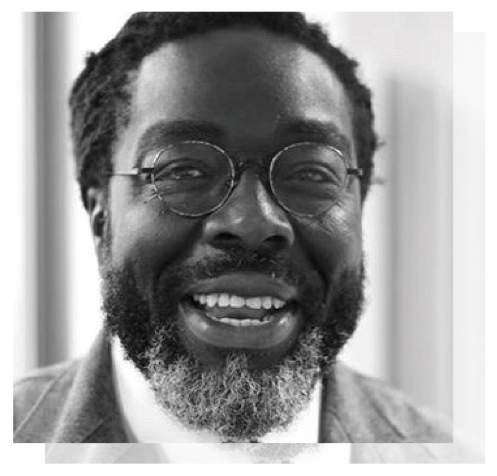 A black and white profile picture of Lord Victor Adebowale who smiles at the camera