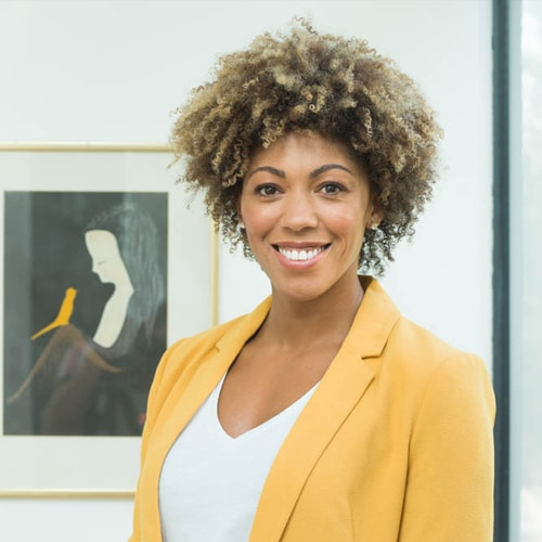 Dr Zoe Williams looks at the camera with a big smile, wearing a yellow suit