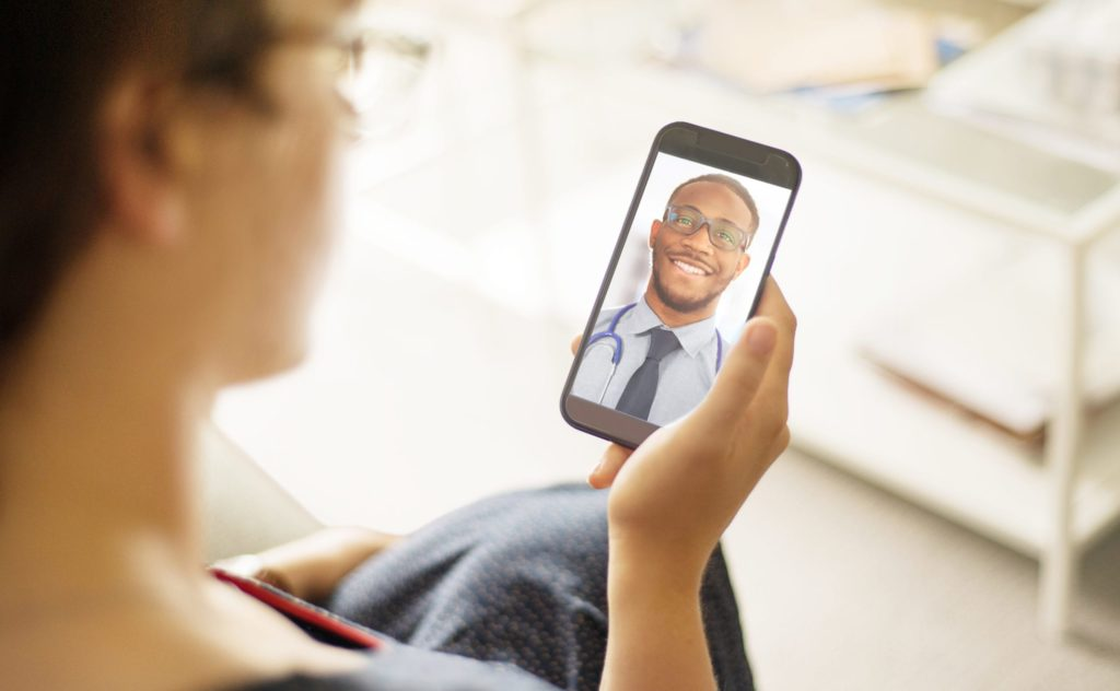 Woman and black doctor having an virtual consultation via a phone