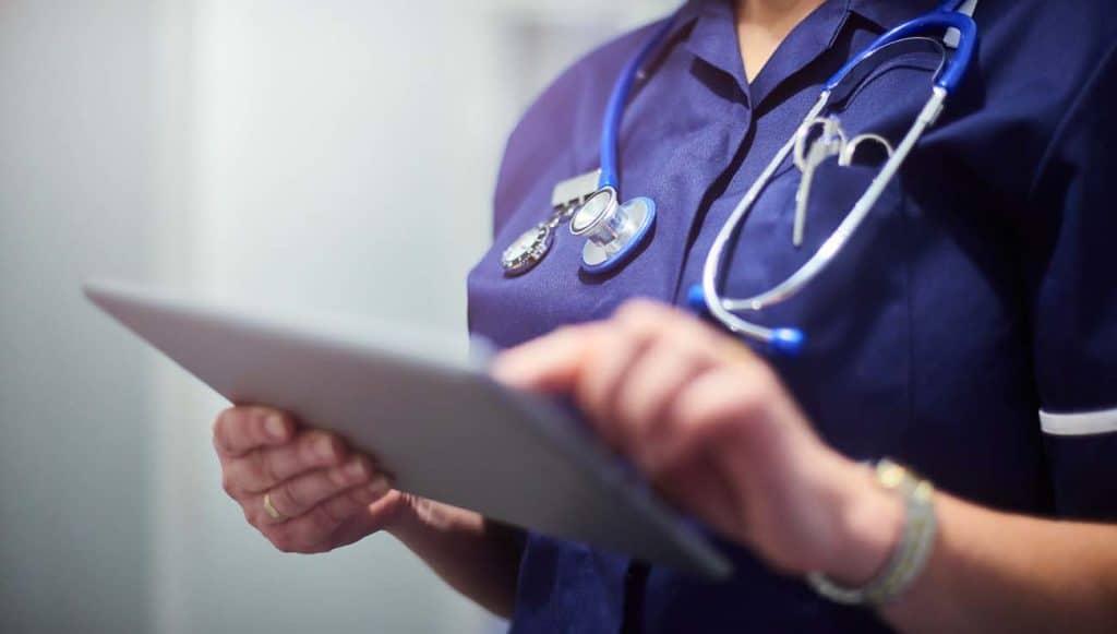 Nurse wearing blue uniform and stethoscope uses tablet