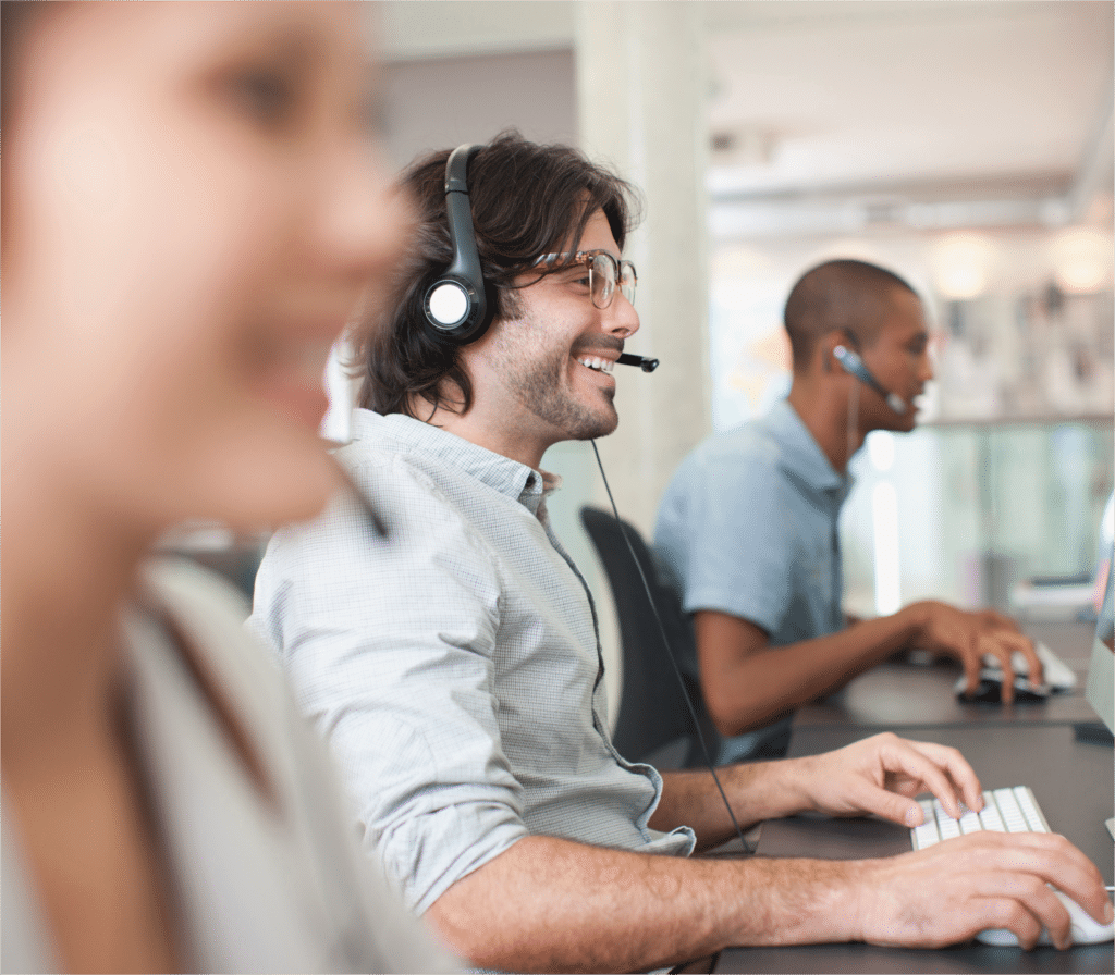 Office workers speak into headsets whilst smiling at their computer screens