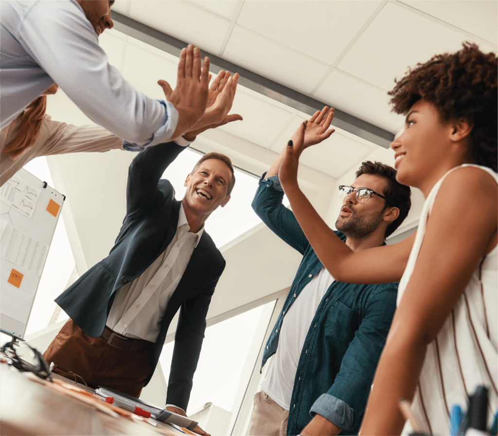 A group of office workers high five each other
