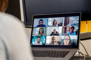 Healthcare professionals appear on a screen attending an online meeting