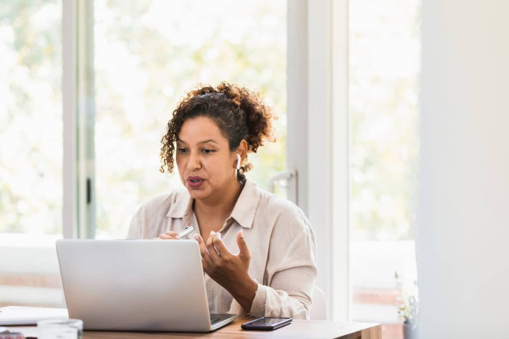 Woman attends virtual support group, gesturing towards a laptop screen