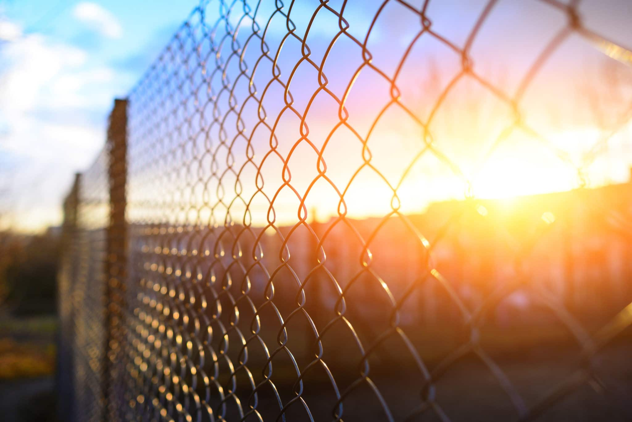 A metal prison fence is in the foregournd with a beautiful sunset behind the fence in the distance.